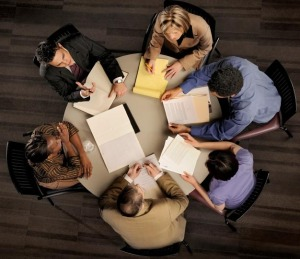 group of confident professional employees in a serious meeting from above